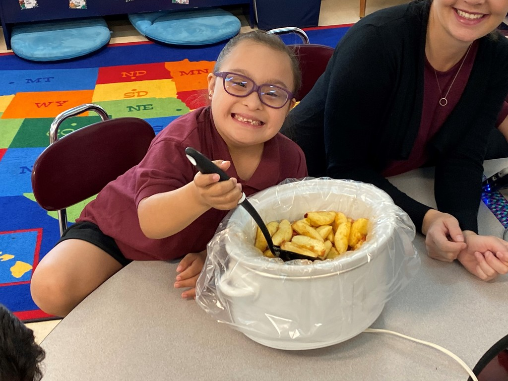 Mrs. Parker's student scooping some apples out.